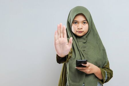 Young Muslim woman holding mobile phone with stop bullying gesture, isolated on gray