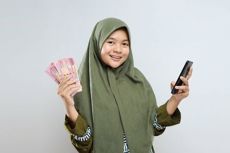 Young asian Muslim Woman happy and excited expressing winning gesture holding mobile phone and money. Successful and celebrating on gray background