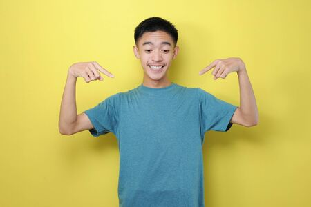 Portrait surprised attractive Young Asian man open mouth pointing index fingers on yellow background, advertise new product or showing drop in prices concept