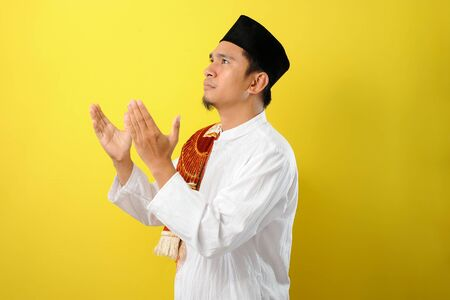 Young Asian Muslim man praying look away raising his hand with muslim dress, isolated on yellow background
