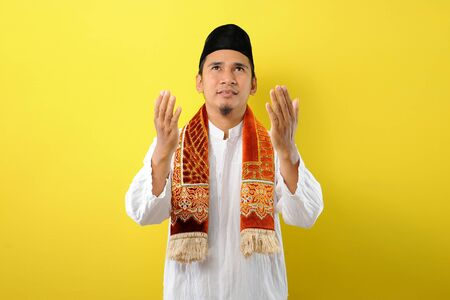 Young Asian Muslim man praying look away raising his hands with muslim dress, isolated on yellow background