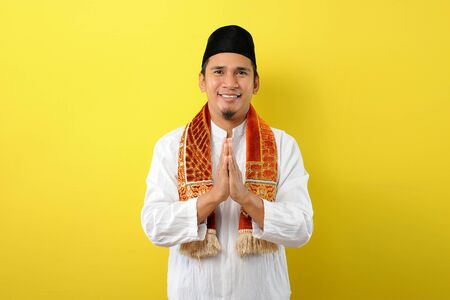 Young Asian Muslim man with greeting and welcoming gesture in Ramadhan, Isolated over yellow background