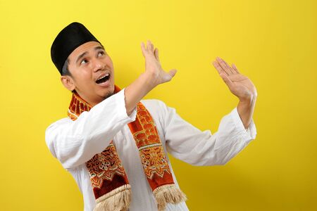A bearded Young Asian Muslim man protecting himself with outstretched hands from something getting to him from above, isolated on yellow background