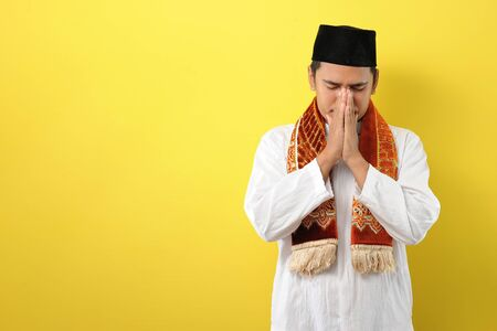 Young Asian Muslim man feel sad with covering his face with hands. Copy space concept, isolated on yellow background Фото со стока