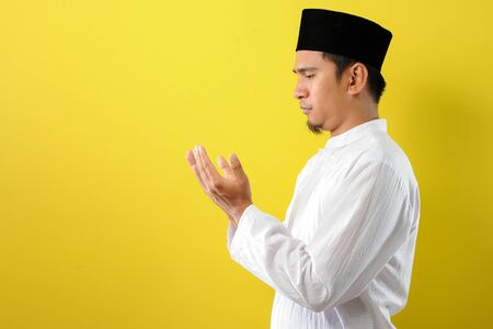 Young Asian Muslim man praying raising his hand with moslem clothes, isolated on yellow background