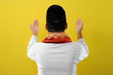 年轻的亚洲穆斯林男子举手祈祷,背景,孤立在黄色背景上