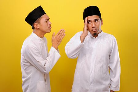 Young Asian Muslim men ignore the apologize of his Muslim's brother. Bad Attitude in Ramadan. Isolated on yellow background
