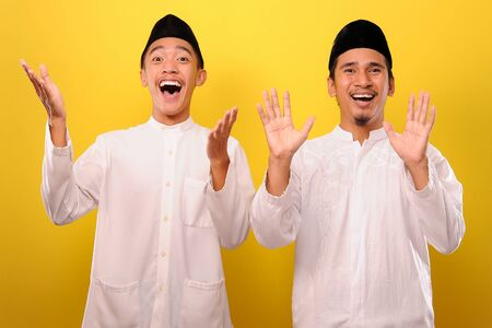 Two Young Asian men very excited look at camera, isolated on yellow background