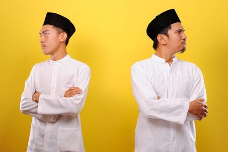 Image of two Young Asian Muslim men hating each other, not greeting each other when Ramadan. Ramadan Concept. isolated on yellow background