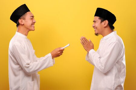 Young Asian Muslim man give alms to other muslim on Ramadan Kareem. It's the best time to give alms to everyone need, isolated on yellow background Banque d'images