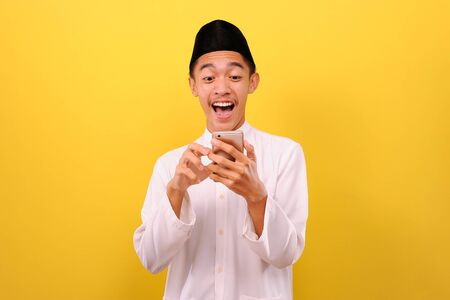 Happy Excited Young Asian Muslim man wearing moslim clothes holding mobile phone look at phone screen, isolated on yellow background