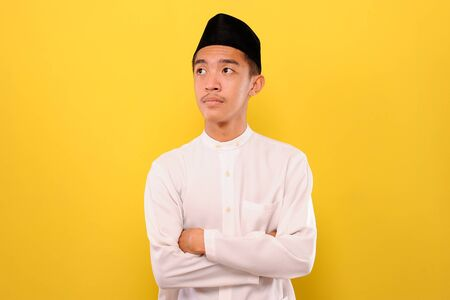 A serious young Asian Muslim man look away and crossed arms, isolated on yellow background Stock Photo