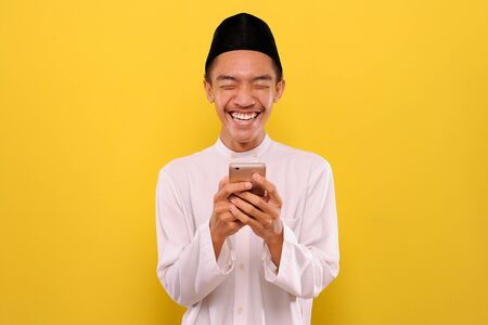 Young Asian Muslim man read funny messages on smartphone, isolated on yellow background