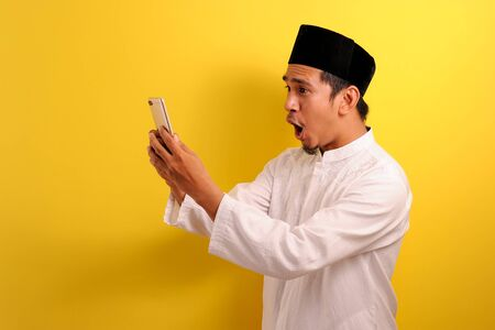 Happy Shock Young Asian Muslim man wearing muslim clothes holding mobile phone look at phone screen, isolated on yellow background