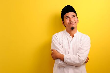 Dreamy Young Asian Muslim man look up with a copy spase, isolated on yellow background