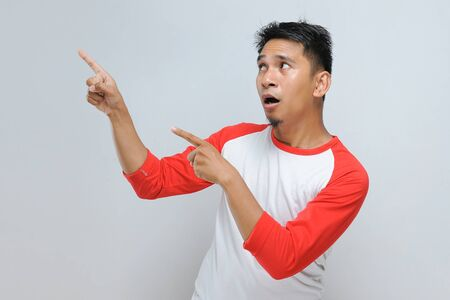 Portrait of shocking Young handsome Asian man pointing at copy space isolated over gray background
