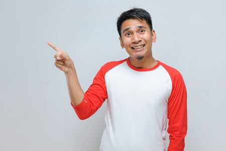 Portrait of excited Young handsome Asian man pointing at copy space isolated over gray background Zdjęcie Seryjne