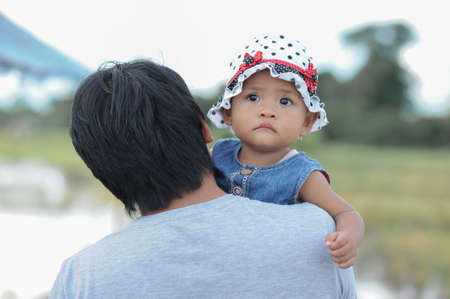 Cute Asian baby girl in his dad's arm wearing hat with polka dots. Father tote his son. Adorable toddler.