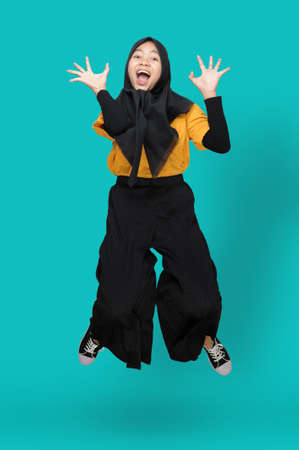 Funny of Young Asian Muslim girl jump over blue background with ridiculous expression.