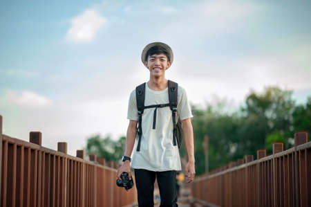 Young male traveler photographer smiling walking on wooden bridge with backpack and holding a camera, Local traveler