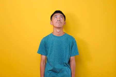Portrait disappointed young asian man with lazy gesture ignoring what he see, looking at copy space, isolated on yellow background