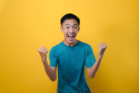 Portrait of happy young Asian man excited raising both his hands, isolated on yellow background