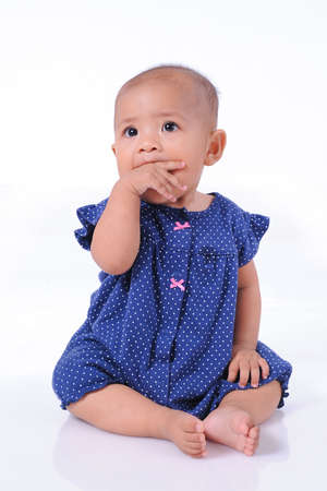 Cute beautiful Baby girl blue shirt chewing his hand, isolated on white background