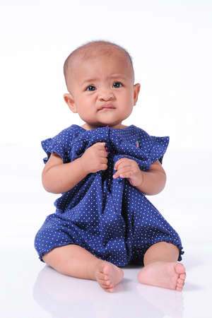 Adorable little baby girl sitting on the white floor, on white background isolated