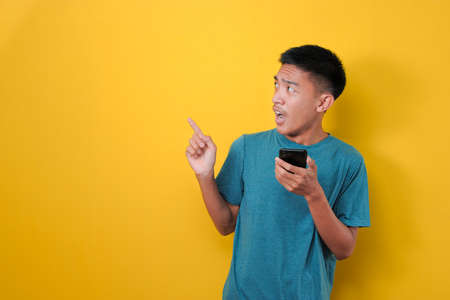 Young Asian Man with shock face holding a mobile phone, pointing and looking at copy space, isolated on yellow background