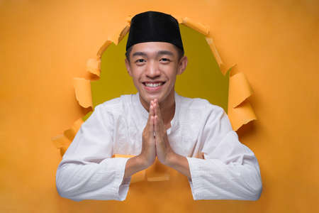 Asian muslim man smiling and shows greeting gesture poses through torn yellow paper hole, wearing muslim cloth with skull cap, welcoming gesture to celebration of Ramadan or Eid Al-Fitr.