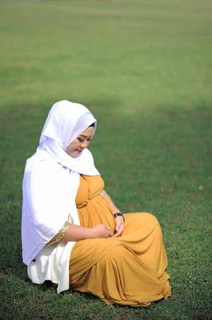 Pregnant Asian muslim woman relaxing in the park Standard-Bild