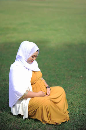 Pregnant Asian muslim woman relaxing in the park Фото со стока