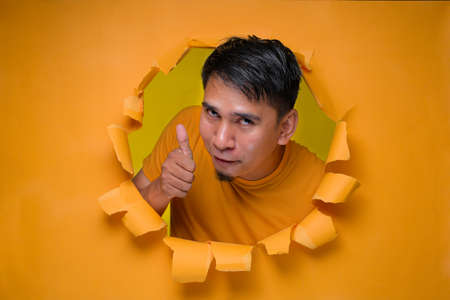 Young entertaining man through torn yellow paper hole showing thump up with facetious of content and happiness. Concept of satisfaction with quality and recommendation