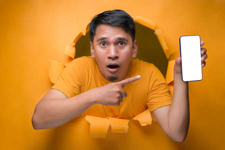Young Asian teenager man with shock face poses through torn yellow paper hole, showing mobile phone with blank white screen display for a copy space. on yellow isolate Banque d'images