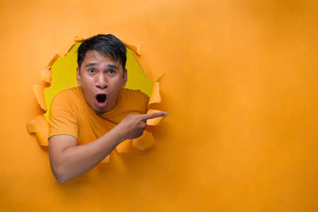 An Excited Asian man with shock face pointing a copy space, poses on torn paper hole.