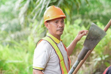 Asian palm oil farmer standing wearing safety helmet and holding harvesting tool palm oil at palm oil plantation