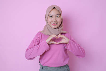 Young Muslim Asian woman showing romantic shapes heart gesture expresses tender feelings wears casual muslim clothes poses against pink background. Care concept