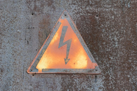 Warning, high voltage on the old metal wall  photo