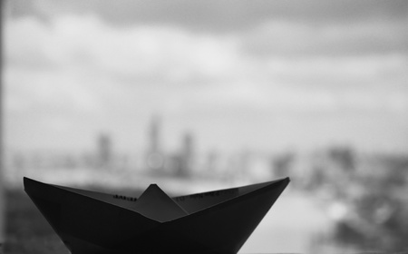 a paper boat floating over the city skyline photo