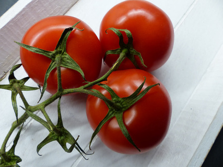 Fresh vine tomatoes on a wooden plate