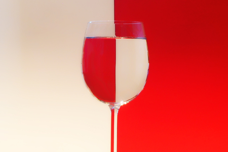 A wine glass with red and white background