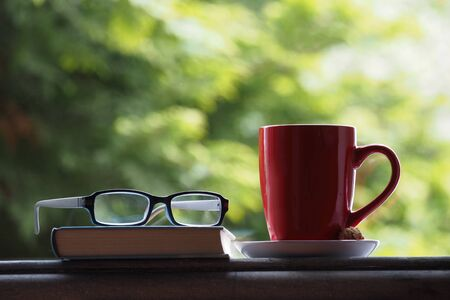 A coffee cup, glasses and a book