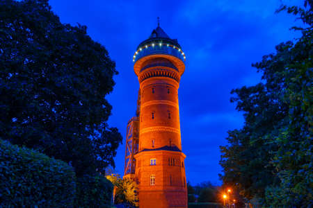 Illuminated historical water tower in Styrum in Germany at night