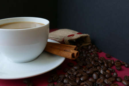 Coffee in a cup with cinnamon and coffee beans