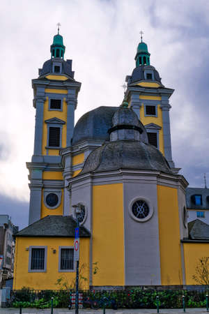 Historical yellow baroque church in the old center of Dusseldorf Imagens
