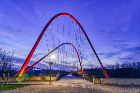 Public park with an illuminated bridge in Gelsenkirchen at night