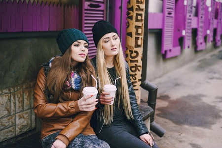 fashionably: two beautiful girls walk around town fashionably and stylishly dressed with a Cup of coffee