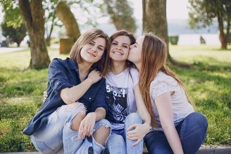 tre belle ragazze che camminano nel parco e scattare foto sul telefono