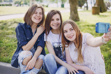 Drei schöne Mädchen, die im Park gehen und Fotos auf Ihrem Telefon machen Standard-Bild - 61113481