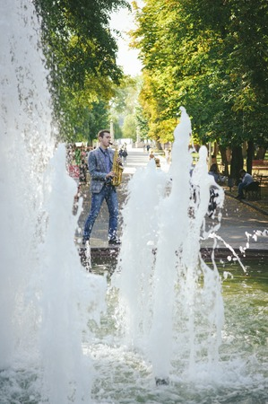 busker playing the saxophoney and near the fountains Stock Photo
